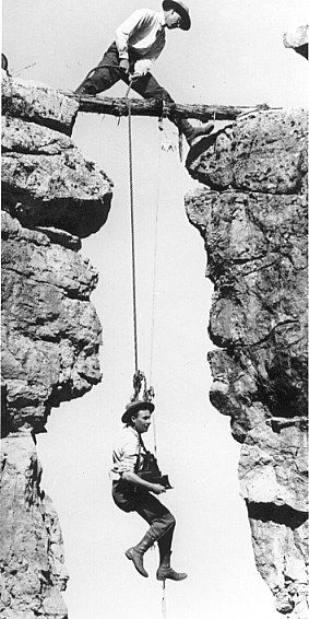 Kolb Brothers, Grand Canyon    Emery lowering Ellsworth down on their famous exploration of Cheyava Falls! Ellsworth Kolb holding camera & suspended by rope. Emery above on log above.     1913 photo.