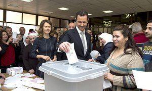 El presidente sirio, Bashar al-Assad emita su voto junto a su esposa Asma (izquierda) en un colegio electoral en Damasco.