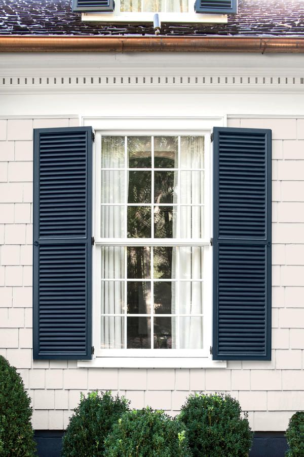 """On a Colonial, this warm white and grayed- down navy make a timeless match. It has a touch of New England formality but works in a small Southern town."" —Catherine Sloan, Catherine Tracy Sloan, Nashville and Memphis  Siding: Polo Mallet White (RL1051)"