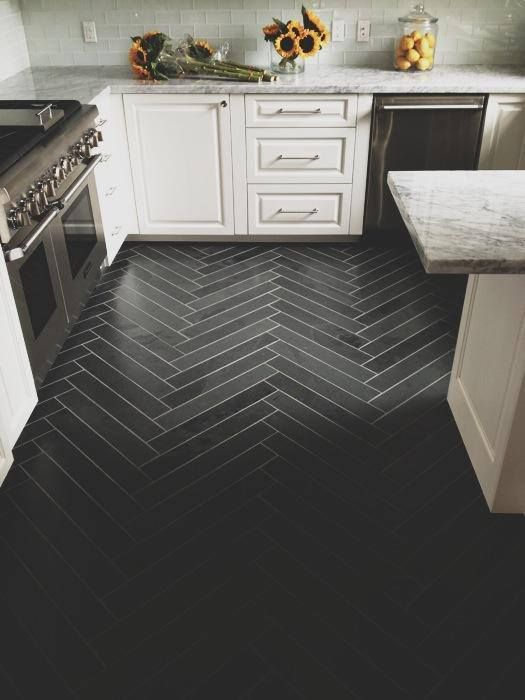 Herringbone tile floor, Dark tile with lighter grout.  White cabinets and translucent glass backsplash lighten the mood.  Modern take on classic herringbone pattern.