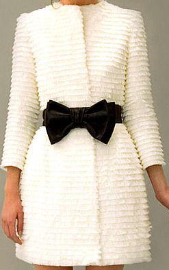 white ruffled coat & black bow.