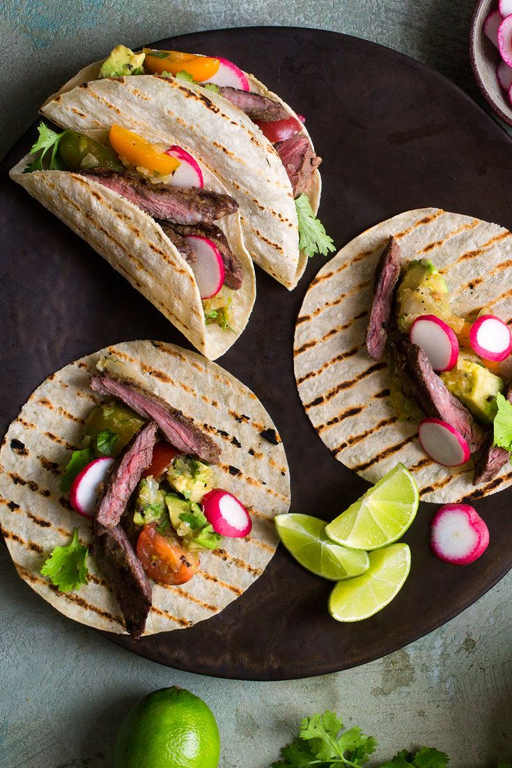 NYT Cooking: In this supremely summery taco recipe, chile-rubbed grilled steak is topped with a spicy tomato-avocado salsa before being rolled into warm corn tortillas. Grilling the onions, garlic and jalapeño for the salsa adds a concentrated sweetness, while lime zest keeps everything sharp and bright. If you don't have access to a grill, feel free to use your broiler.