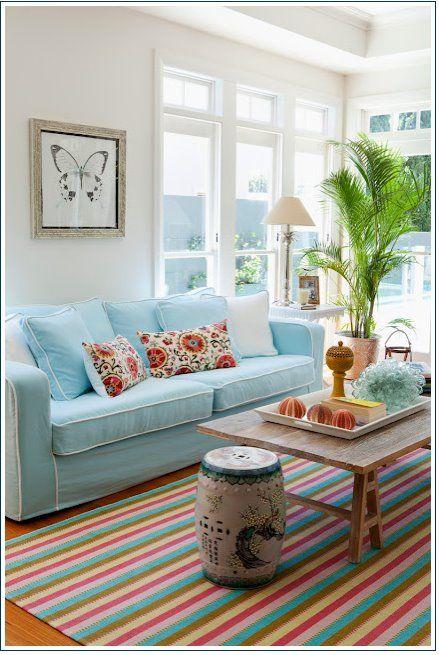 Sala de estar que é a cara do verão, cores pastel com tapete colorido.
