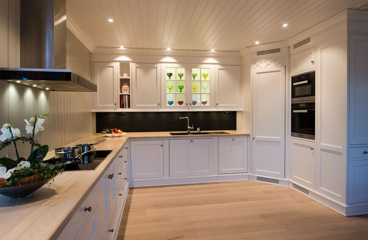 Hand painted white kitchen in solid pine from Os Trekultur. Worktop in stained and varnished oak. Integrated appliances and good storage solutions. Cabinet for oven and microwave. Corner fridge providing ample space for food.