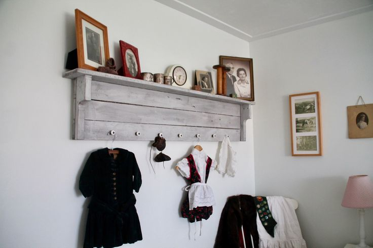 "Shelf constructed of rough lumber and knobs from an old dresser I updated. Shelf was stained Kona, painted over in white and sanded. Great way to display old children clothes including my grandfathers ""velvet suit""."