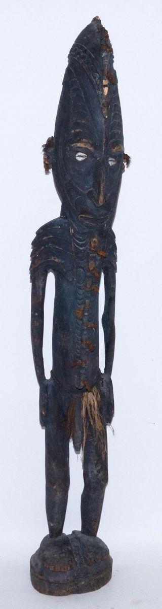 Een gestileerd houten Sepik sculptuur van een staande man bezet met sagoblad vezel en ogen vervaardigd van kauri schelpen, Papoea-Nieuw-Guinea, tweede helft 20e eeuw