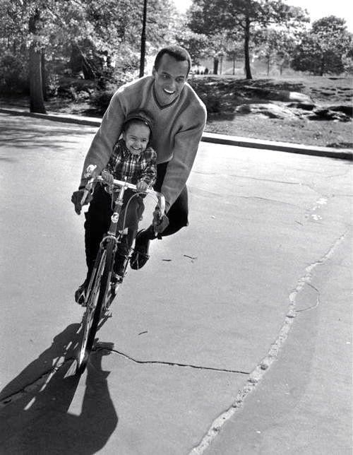 Harry and Shari Belafonte ride a bike.