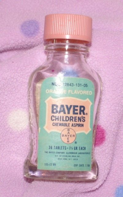 This vintage glass bottle has a pink and blue label and a pink screw-on cap. The glass itself has Bayer Aspirin imprinted on the sides.    This