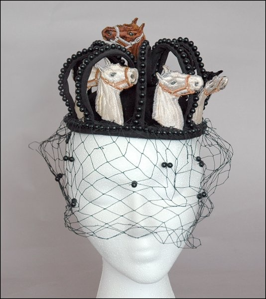 Bes-Ben 'Horse Head' hat   United States, ca. 1967-1968   Black velvet slightly domed hat with eight standing ribs edged with black beads. Between each rib is an embroidered white horse head   Emerging from the crown, where the ribs meet is an embroidered brown horse head   Black veil