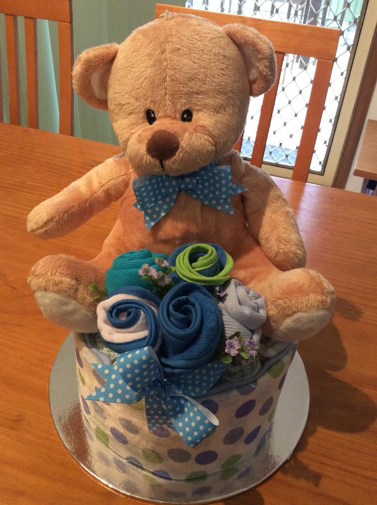 "Teddy sitting in amongst the singlet and bib ""flowers"" atop a ""cake"" of nappies all wrapped in a bunny rug."