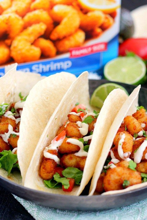 These Cilantro Lime Popcorn Shrimp Tacos are filled with crispy popcorn shrimp, a zesty cilantro lime sauce, and topped with a cilantro cream drizzle. Easy to make and ready in just 20 minutes, this flavorful dish will be the hit of your dinner table! #ShrimpItUp #ad