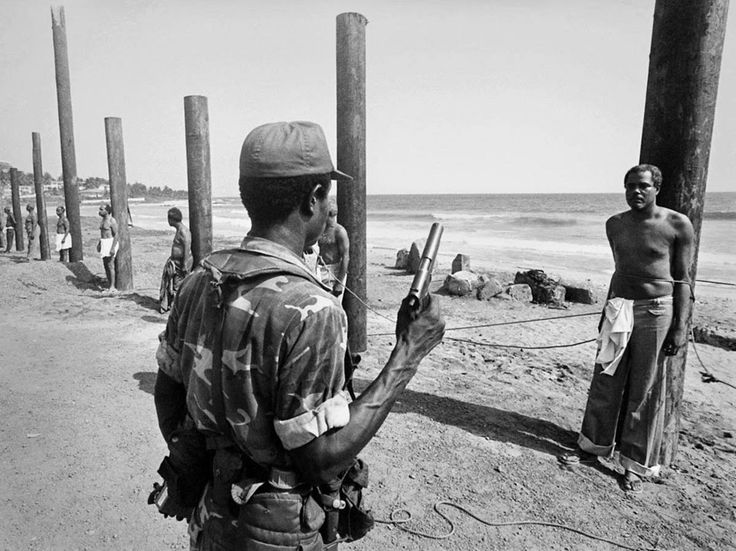 A Liberian army soldier stands ready to execute a former cabinet minister following the 1980 coup.