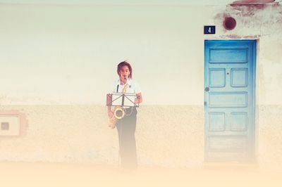 Caroline Stephensen - Toner i bris. Blue door and musician playing trumpet.