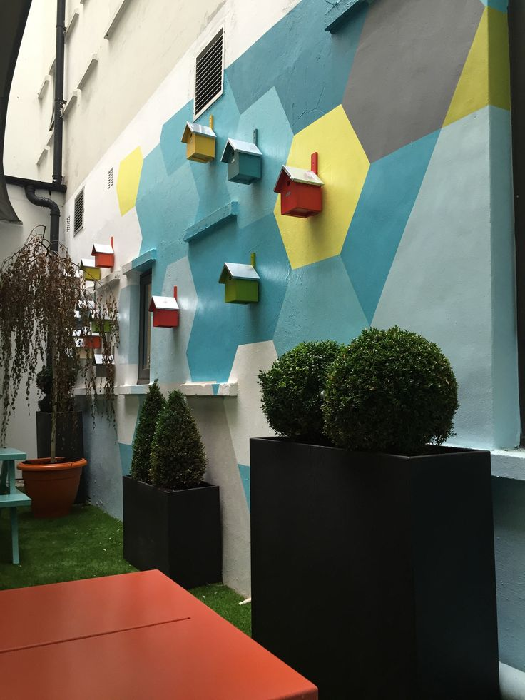 Shand House, Cardiff – transformation of communal courtyard for student accommodation. The feature murals had a funky and vibrant look, incorporating fun elements from nature including brightly painted bird boxes.  #exteriormural #handpainted #educationmural