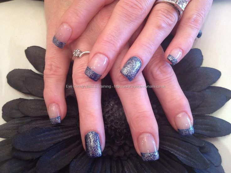 Acrylic nails with blue polish and silver glitter