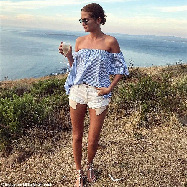 Chic: The reality star turned fashion designer looked typically stylish in a blue gingham bardot top and white hotpants as she posed in front of a picturesque back drop with a glass of wine