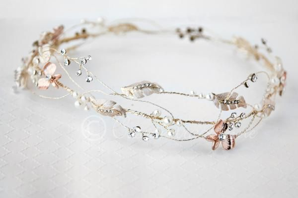 This delicate bridal hair wreath is designed with rose gold cast flowers and light gold leaves and wire. Sprays of ivory pearls and rhinestones are added along