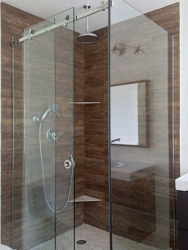 frameless corner sliding shower glass enclosure with two fixed panels and one movable panel in the