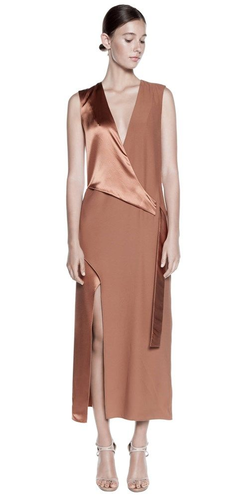 Sleeveless silk satin dress with v neck, belted detail at front, high slit on right of front and back, exposed slit at top centre back with zipper closure at centre back.