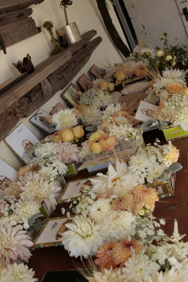 Cigar boxes used as centerpieces for a wedding dinner table.