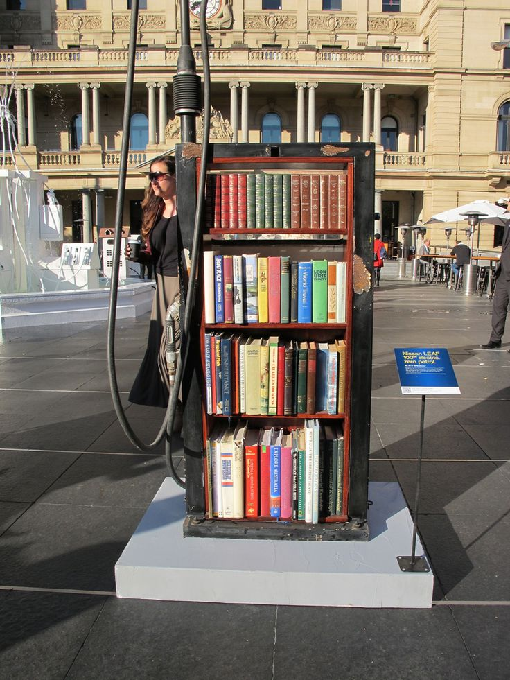"""Book delivery from gasoline delivery... -- """"Bookcase Petrol Bowser -- An art installation by Nissan for their [100% electric] LEAF model in Sydney, Australia showing how petrol bowsers might be used in a 'World Without Petrol'."""" [Click through to a link for the """"World Without Petrol"""" video, showing other clever uses for gasoline pumps made obsolete by LEAF.]"""