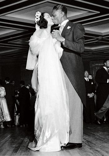 Nat King Cole and Maria Ellington share a kiss while dancing at their wedding reception in Harlem, New York on 28 March 1948. Cole and Ellington's wedding ceremony was held on Easter Sunday at Harlem.