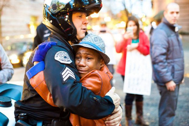 Sgt. Bret Barnum and Devonte Hart hug during a hectic Ferguson rally in Portland. Johnny Nguyen/Special to the Oregonian