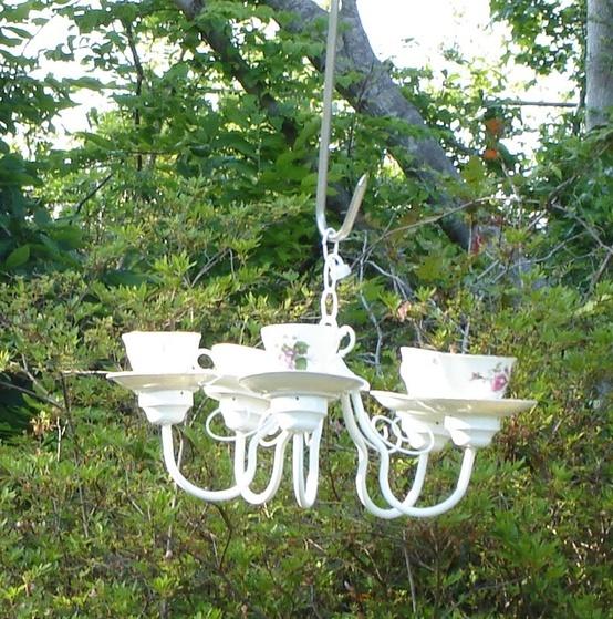 oude kroonluchter met servies voor de vogeltjes in de tuin.