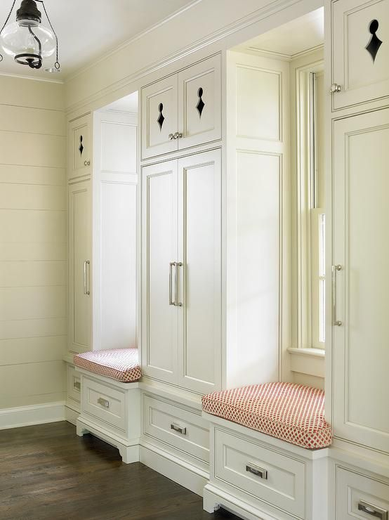 Beautiful cottage mudroom features two built in window seat benches accented with red trellis seat cushions and sat between built in cabinets fitted with aged nickel pulls and accented by cutouts on the top cabinet doors.