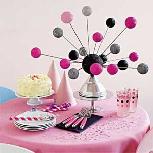 Derek McLane might be the set designer for the musical Grease on Broadway, but his stellar centerpiece is simply out of this world. Inspired by the hues of the iconic Pink Ladies and T-Bird jackets, McLane turned a funnel on its end and attached painted foam balls to it with skewers. We love it for a kids' party -- or any bash that needs an eye-popping splash of color.