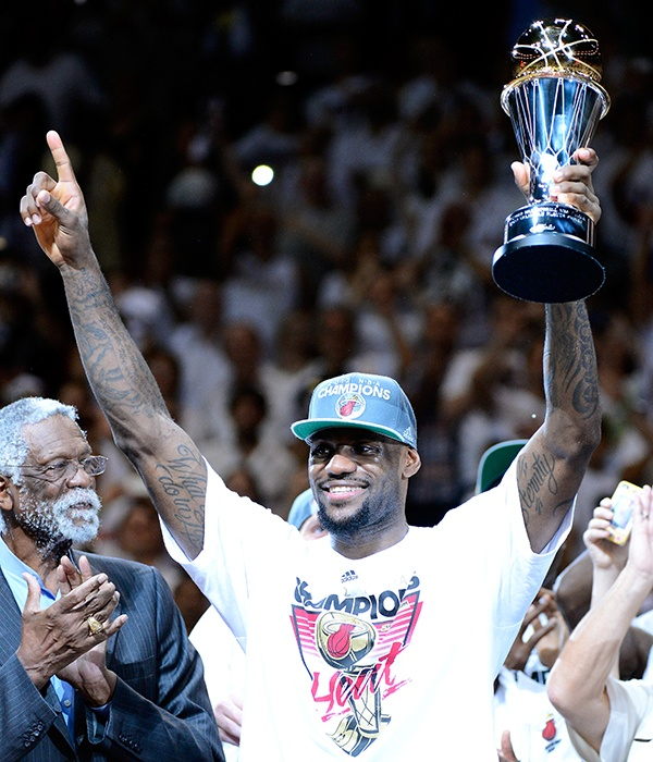 """JUNE 21: THE DECIDER -- LeBron James hoisted the Larry O'Brien Trophy for the first time after Miami's NBA Finals victory over Oklahoma City. Pilloried for two years after announcing his move from Cleveland to South Beach in a tasteless TV special called """"The Decision,"""" James won Finals MVP honours after leading all playoff scorers with 30.3 points per game, 9.7 rebounds and 5.6 assists. The Heat star also captured the regular-season MVP trophy. (Photo by Ronald Martinez/Getty Images)"""
