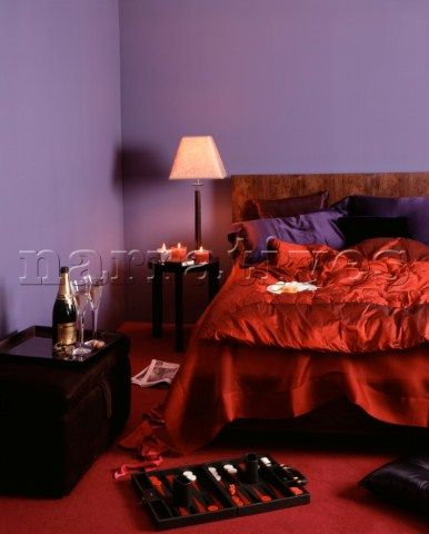 Backgammon set in purple bedroom with red contrasting quilt and champagne