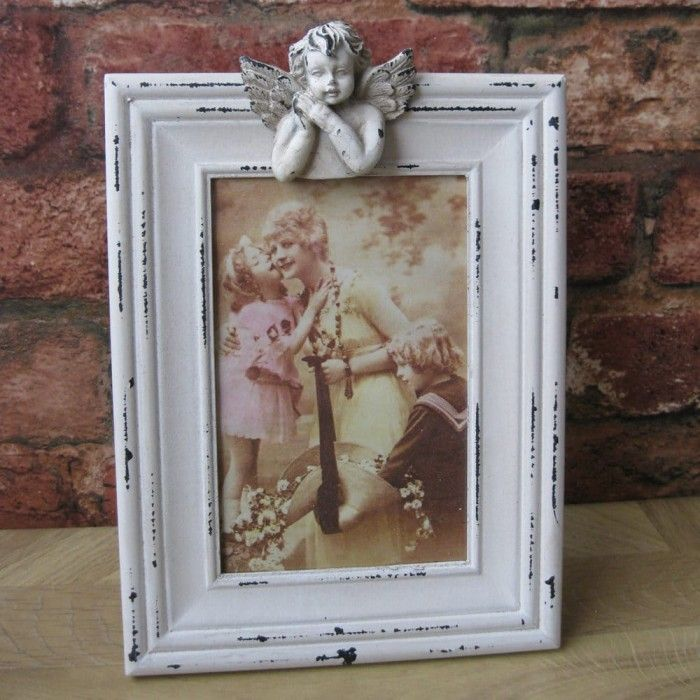 This is a beautiful Victorian style Angel Standing Photo Frame features one little cupid on the top. This pretty resin photo frame is finished with a shabby chic cream distressed paint effect. The picture frame comes with a stand at the back.