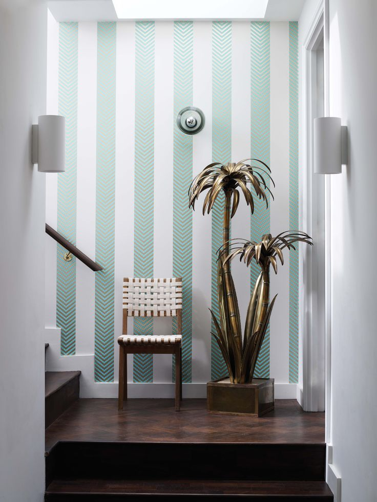 Matthew Williamson in collaboration with Osborne & Little. The Nevis wallpaper from the 2015 Samana collection. A chevron stripe enlivened with tiny glistening beads. A white woven chair against the striped Nevis wallpaper wall. A white woven chair against the striped Nevis wallpaper wall.