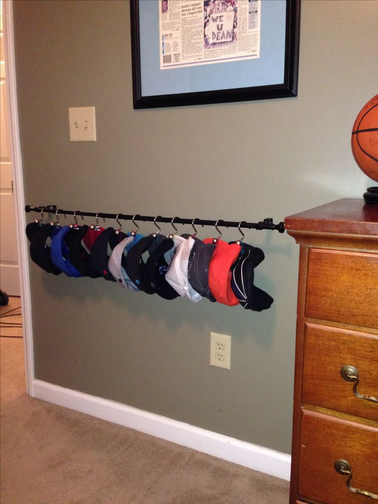 Diy hat rack i used a curtain rod shower curtain hooks for Hat hanging ideas