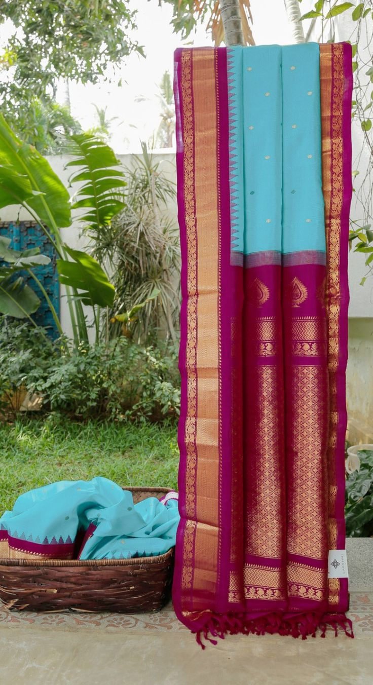 This gadwal silk is in sky blue with gold zari bhuttas all over. The complementing border and pallu are in magenta intricately woven with gold zari making it a stylish traditional sari