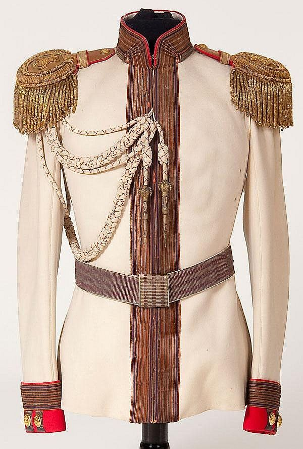 A FINE IMPERIAL RUSSIAN HORSE GUARD REGIMENT OFFICER'S TUNIC OR 'KOLLER', ca 1900. White boiled wool tunic with red cuffs and piping. Silver bullion braid mixed with orange and bordered in blue trim on collar, front and cuffs. Collar and cuffs also display silver bullion Litzen, those on the cuffs with gold double-headed eagle buttons. Complete with gold bullion fringed epaulettes faced in red with applied gold tone crown and cipher of Nicholas II. The left chest is tailored with award ...
