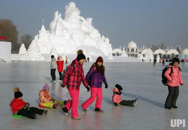 Chinese women pull their young kids on min-sleds across a frozen lake at the 33rd Harbin International Ice and Snow Sculpture Festival that…