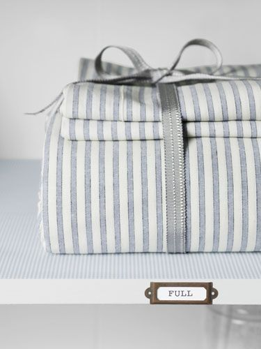 No more toppling sheets! (Or lost pillowcases!) Bundle your sheet sets together and label to separate the fulls from the queens.    #storage #organization