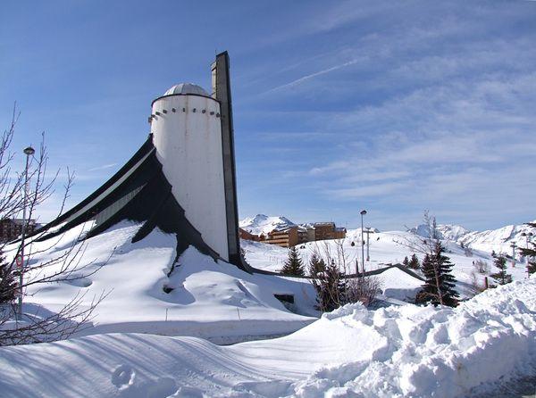 Petite visite à l'église, Notre Dame des Neiges, conçue par Jean Marol pour figurer la tente qu'Abraham planta dans le désert. On dit aussi que la forme de l'église reproduit la silhouette de la Meije, sommet de la région culminant à 3984 mètres.
