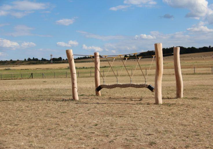 Dětské hřiště u letiště Točná. Velké oplocené hřiště na klidném místě u lesa s pískovištěm, dřevěnými prolézačkami a velkým volným prostorem k různým hrám.