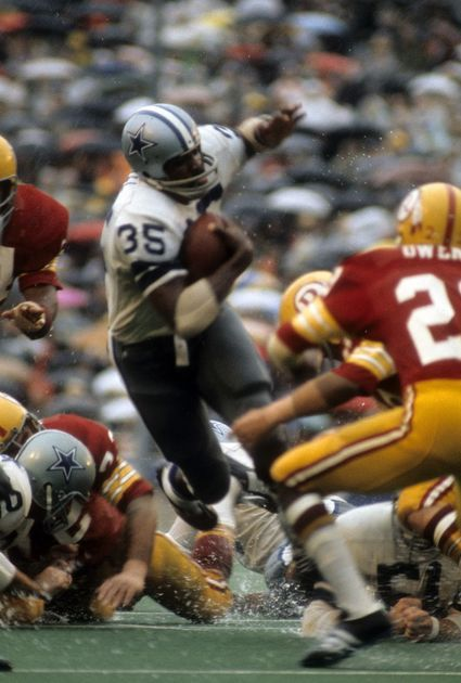 Running back Calvin Hill #35 of the Dallas Cowboys carries the ball against the Washington Redskins at Texas Stadium, 12/21/69. Photo by Focus on Sport/Getty Images