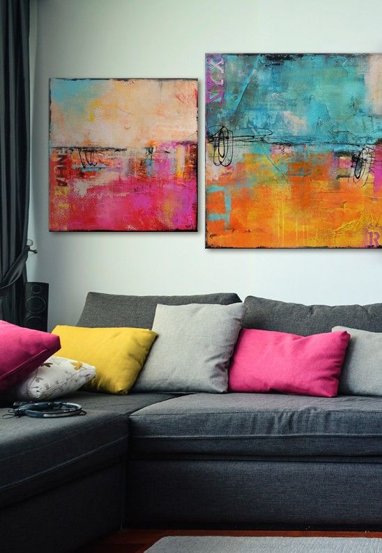 Eye-popping abstract pieces match the throw cushions in a neutral coloured living room