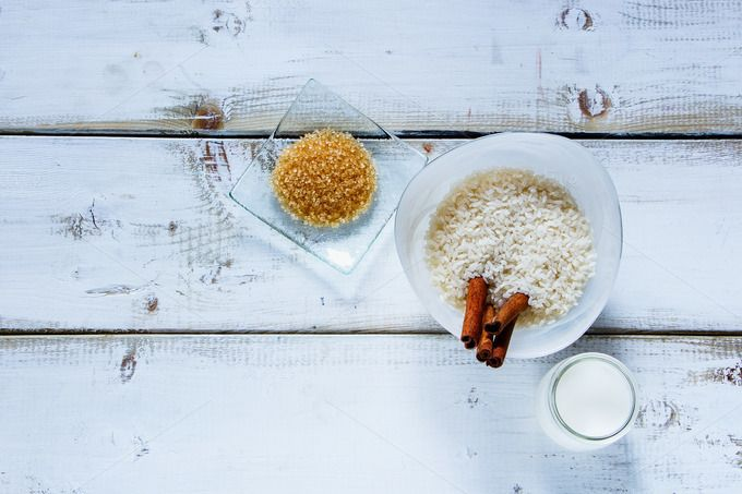 #Ingredients for making rice pudding  Old table with ingredients for making rice pudding. Bowl of white uncooked rice brown sugar cinnamon sticks and jug of milk or cream over wooden background. Top view space for text