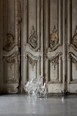 Glass chandelier on floor with ornate rococo style distressed wooden panelled wall -- from John Day