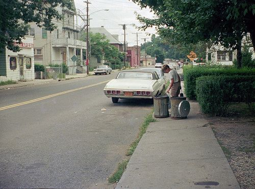 New scan of a friend poking through old-style metal garbage cans while holding his 1950s Brownie camera. A 1960s Chevy with New York plates ...