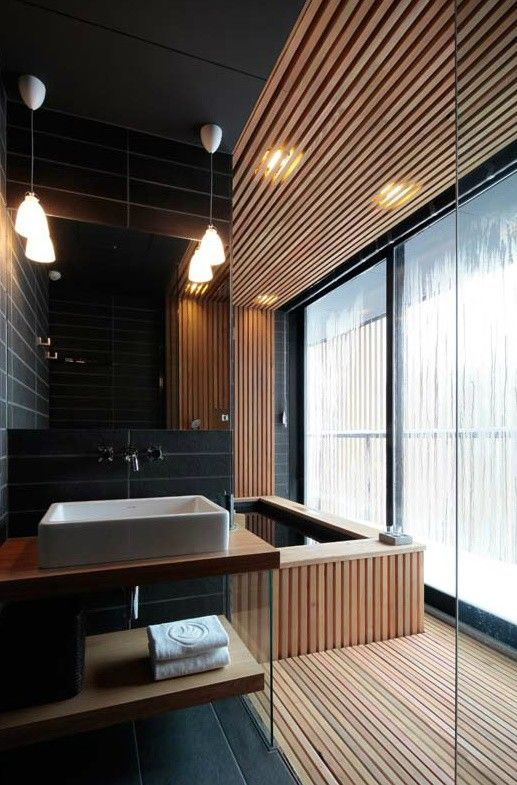 This room from another house, shares its theme with the Queenscliff residence. Timber paneling is used to not only frame the bathtub but also to highlight the room zones.