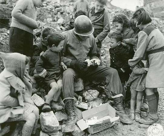 a soldier shares candy with German children during WWII