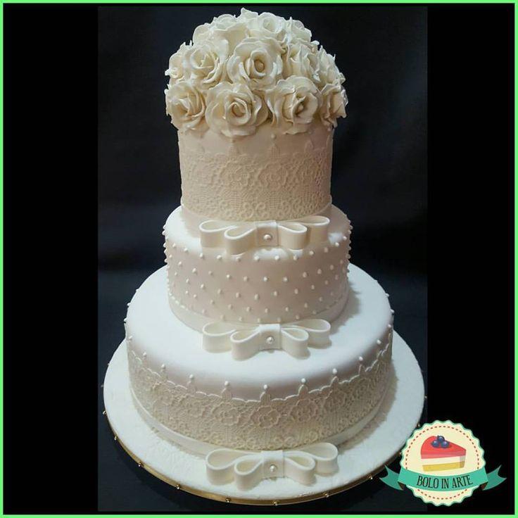 Bolo de casamento de três andares, decorado com renda comestível, poás de glacê real, laços de pasta americana e topo de rosas brancas modeladas em massa de flores.