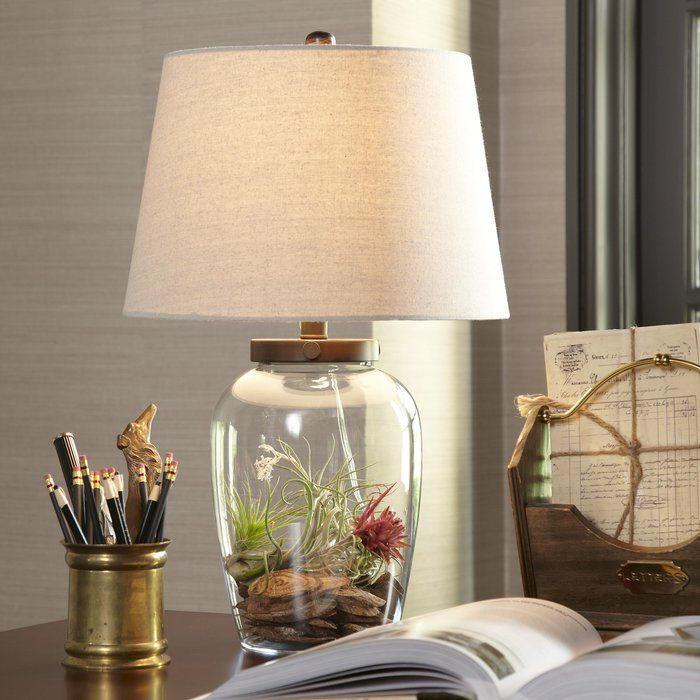 The Wallington Table Lamp's linen shade and clear glass base evoke timeless simplicity. The hollow base allows for an endless number of styling choices, from crafting a terrarium landscape to showcasing your seashell collection.